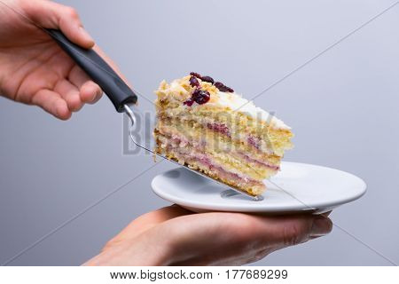 Cake with cherry on a white plate.waiter placing slice of cake to plate with cake server.