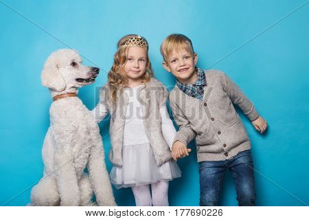 Little princess and handsome boy with Royal poodle. Love. Friendship. Family. Studio portrait over blue background