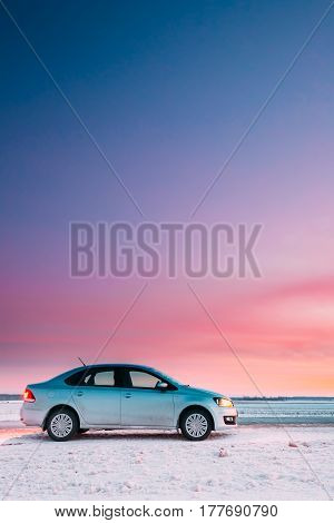 Gomel, Belarus - January 26, 2017: Volkswagen Polo Car Sedan Parking On A Snowy Roadside Of Country Road On A Background Of Dramatic Sunset Sky At Winter Season. There are spots of dirt on a car door