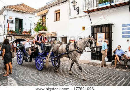 Mijas, Andalusia, Spain - July 12, 2014 : Horse and carriage rides for tourists through the streets of a typical Andalusian White Village of Mijas Pueblo in Southern Spain