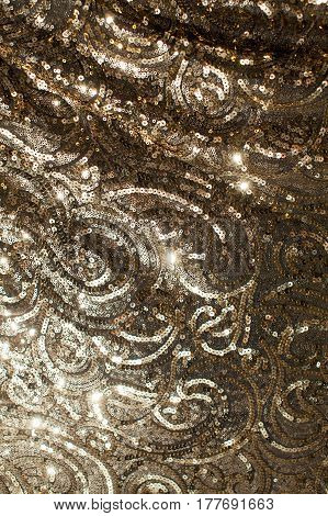 Beautiful abstract sparkles glitter background. Brilliant background. Brilliant gold fabric texture. Paillettes on fabrics. Background from paillettes.