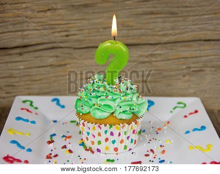 question mark birthday candle on cupcake with green icing and sprinkles on white square plate