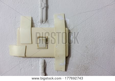 Dirty broken electrical socket with tapes on usable light switch and the small long crack white wall as a background