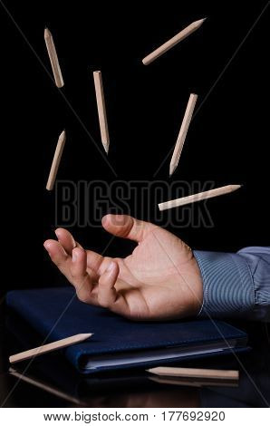 hand with levitating pencils in the office on black background