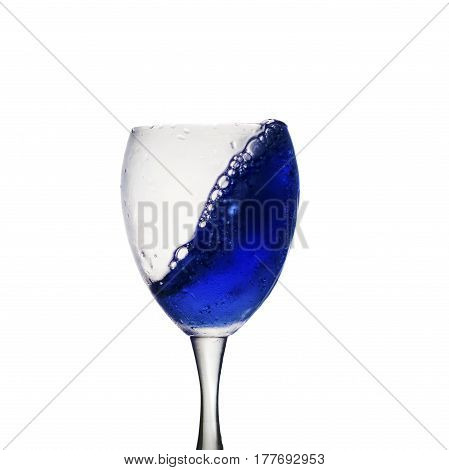 A Blue Drink Is Poured Into Wine Glass Causing A Splash, Isolated On White Background