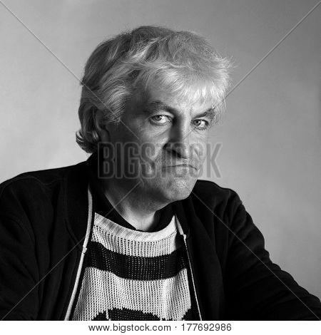Blonde 50 years old man in a black jacket and whitesweater looks directly into the lens. portrait in the style of black and white analog photography.