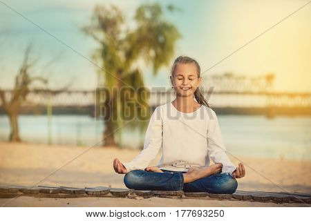 Beautiful little girl sitting in a lotus position on an exotic beach