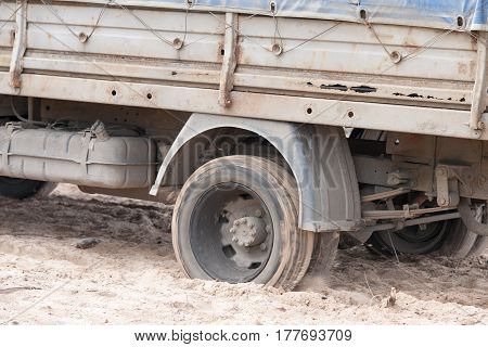 Close up image of a truck wheels slipping in sand