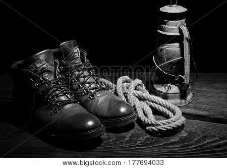 Still life of travel boots old latern kerosine lamp and sailor rope on wooden background.Black and white