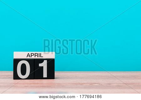 April 1st. Day 1 of month, calendar on wooden table and turquoise background. Spring time, empty space for text.