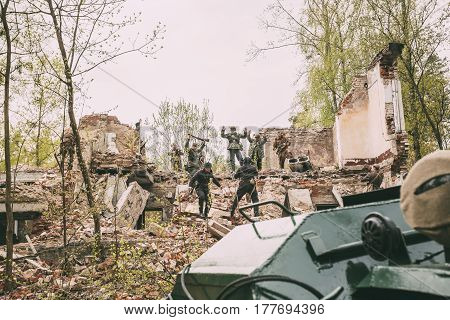 Pribor, Belarus - April 24, 2016: Re-enactors Dressed As Russian Soviet Soldiers Of World War II Performing Mopping-up Operation. German Soldiers With Raised Hands Come Out And Surrender To Captivity