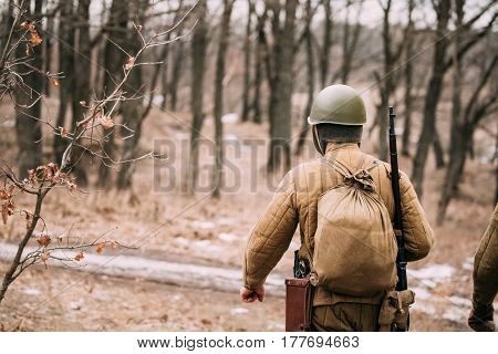 Re-enactor Dressed As Soviet Russian Red Army Infantry Soldier Of World War II Marching Along Forest Road At Autumn Season