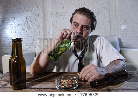 wasted dirty and messy alcoholic man on loose necktie at home living room couch drinking beer bottle getting drunk and intoxicated in alcohol abuse and addiction and alcoholism problem