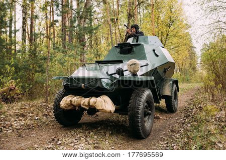 Pribor, Belarus - April 24, 2016: Re-enactor Dressed As Russian Soviet Crew Member Soldier Of World War II Sitting In Armoured Soviet Scout Car BA-64 In Forest And Aiming a Sub-machine Gun at Enemy