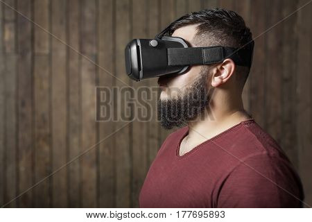 Bearded man with virtual reality glasses standing on the wooden background. Concept of virtual life, games, shopping