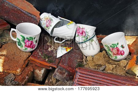 Six colorful old broken cups in the garbage
