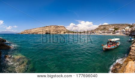Panoramic view of Matala beach and lagoon with sandstone cliffs and turquoise waters of the Libyan Sea near Heraklion in Crete,  Greece, Mediterranean