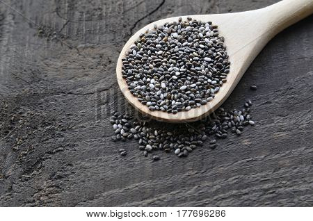 Chia seeds in a wooden spoon on old wooden background.Wooden spoon with chia seeds.Organic chia seeds.Healthy food,superfood or bodycare concept.Selective focus.
