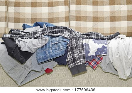 Lot of wrinkled clothes lying on sofa