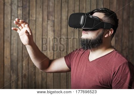 Bearded man with virtual reality glasses standing over wooden background. concept of nosy, curiosity, cognition, study, learning
