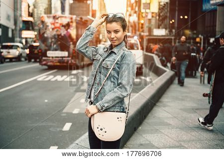 Lifestyle photo of happy young tourist adult woman looking at camera holding bag purse and sunglasses on sunny busy city street