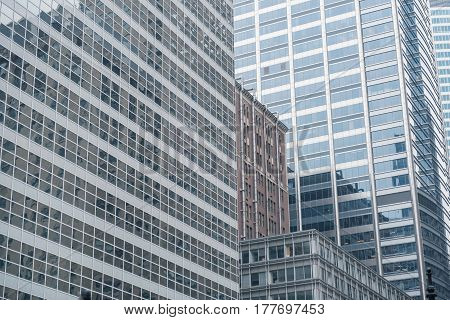 Close up tall buildings situating near each other in business district in United States. Reflex concept
