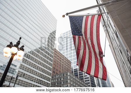 Low angle of american flag flying against background of modern glass multi-storey houses in Chicago, USA