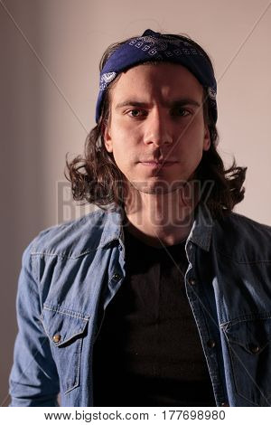 Young man rocker in bandana with long hair. Nice photo.