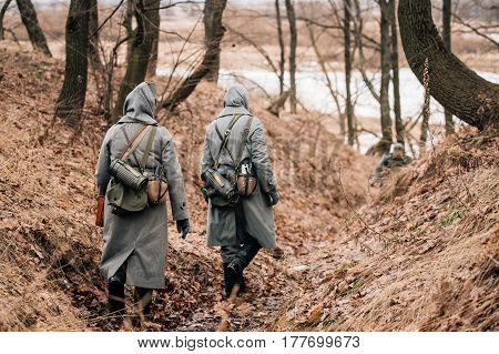 Two Unidentified Women Reenactors Dressed As German Wehrmacht Soldiers at World War II Walks On Forest Trench.