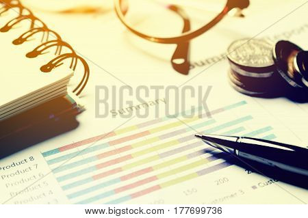 Summary Report And Financial Analyzing Concept, Pen And Notebook With Thailand Coin And Eyeglasses O