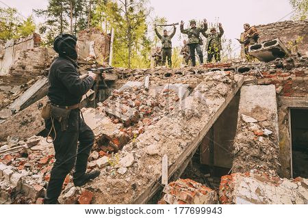 Pribor, Belarus - April 24, 2016: Re-enactor Dressed As Russian Soviet Soldier Of World War II Performing Mopping-up Operation. German Soldiers With Raised Hands Come Out And Surrender To Captivity
