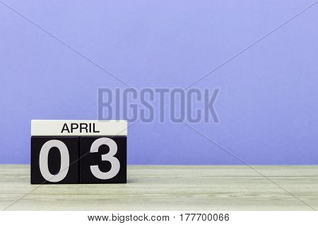April 3rd. Day 3 of month, calendar on wooden table and purple background. Spring time, empty space for text.