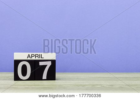 April 7th. Day 7 of month, calendar on wooden table and purple background. Spring time, empty space for text.