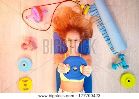 Girl blonde with fitness accessories, top view.