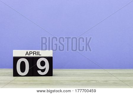 April 9th. Day 9 of month, calendar on wooden table and purple background. Spring time, empty space for text.