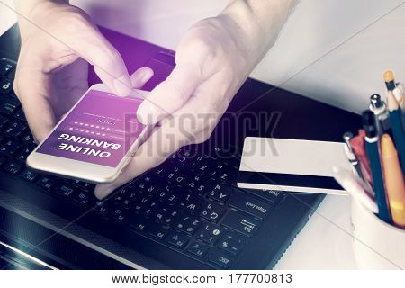 Man's hands using online banking and login username and password with smartphone on desk at home.