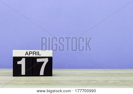 April 17th. Day 17 of month, calendar on wooden table and purple background. Spring time, empty space for text.