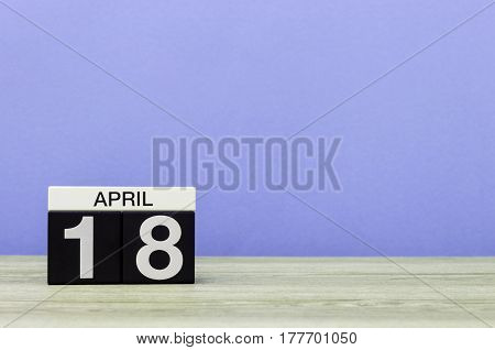 April 18st. Day 18 of month, calendar on wooden table and purple background. Spring time, empty space for text.