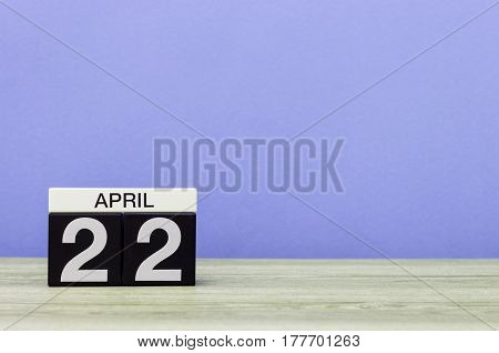 April 22nd. Day 22 of month, calendar on wooden table and purple background. Spring time, empty space for text.
