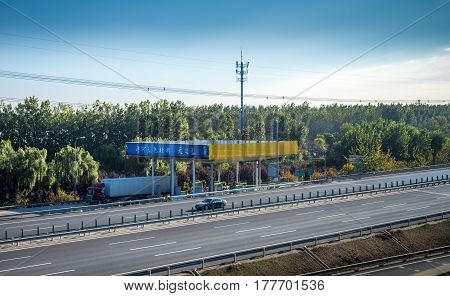 Beijing, China - Oct 31, 2016: Vehicle refueling station or garage along the countryside highway soon after leaving Beijing city. Captured from within a High-Speed Rail (HSR) bullet train traveling at 300 km/h.