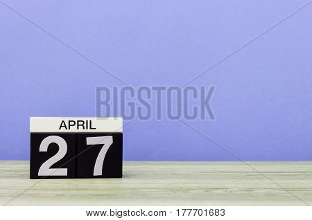 April 27th. Day 27 of month, calendar on wooden table and purple background. Spring time, empty space for text.