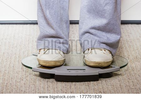 Diet fitness slimming loosing weight concept. Person in tracksuit and sports shoes standing on weighing machine