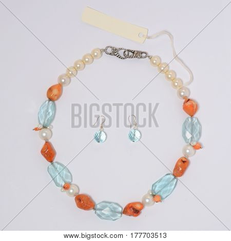 Necklace and earrings of natural stones on a white background closeup