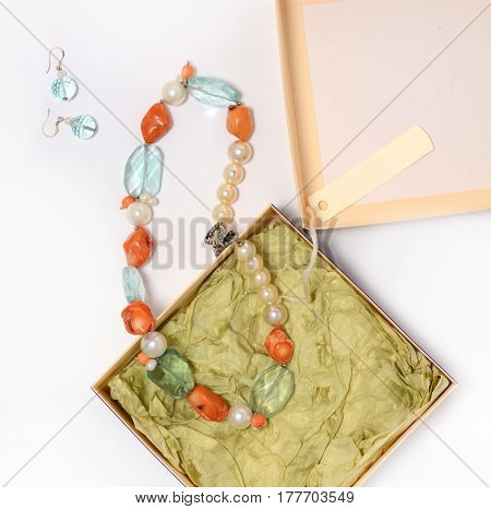 Necklace and earrings of natural stones on a white background closeup in the box