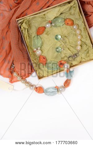 Necklace and earrings of natural stones on a white background closeup in the box red scarf