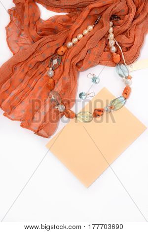 Necklace and earrings of natural stones on a white background closeup with red scarf envelope