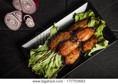 Tasty grilled chicken wings. Dark background. Fast food. Top view