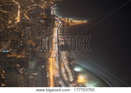 Cars driving along night road between high-rise buildings and sea coast