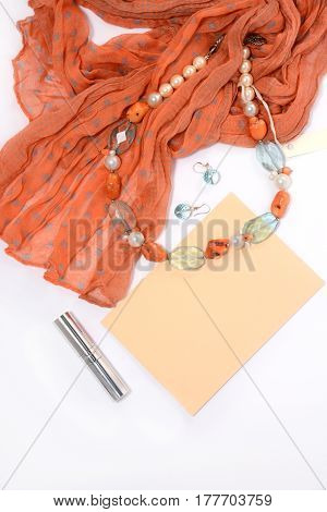 Necklace and earrings of natural stones on a white background closeup with red scarf envelope lipstick