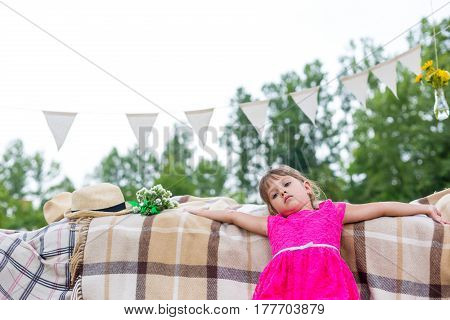 Children in a pink dress sitting on the couch with makeshift equipment